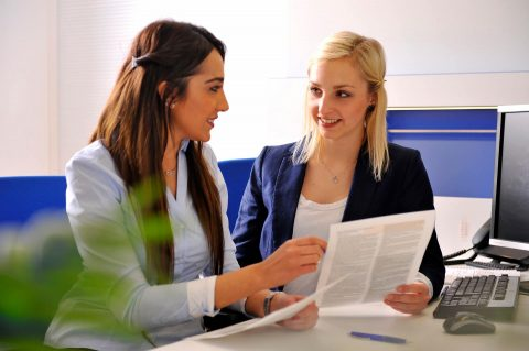 Zwei Frauen in Anzügen besprechen sitzend in einer Büroumgebung ein Dokument