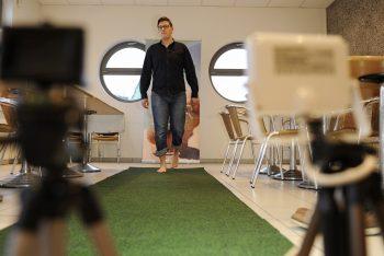 Ein Mann mit hochgekrempelter Jeans schreitet barfuß über einen grünen Teppich